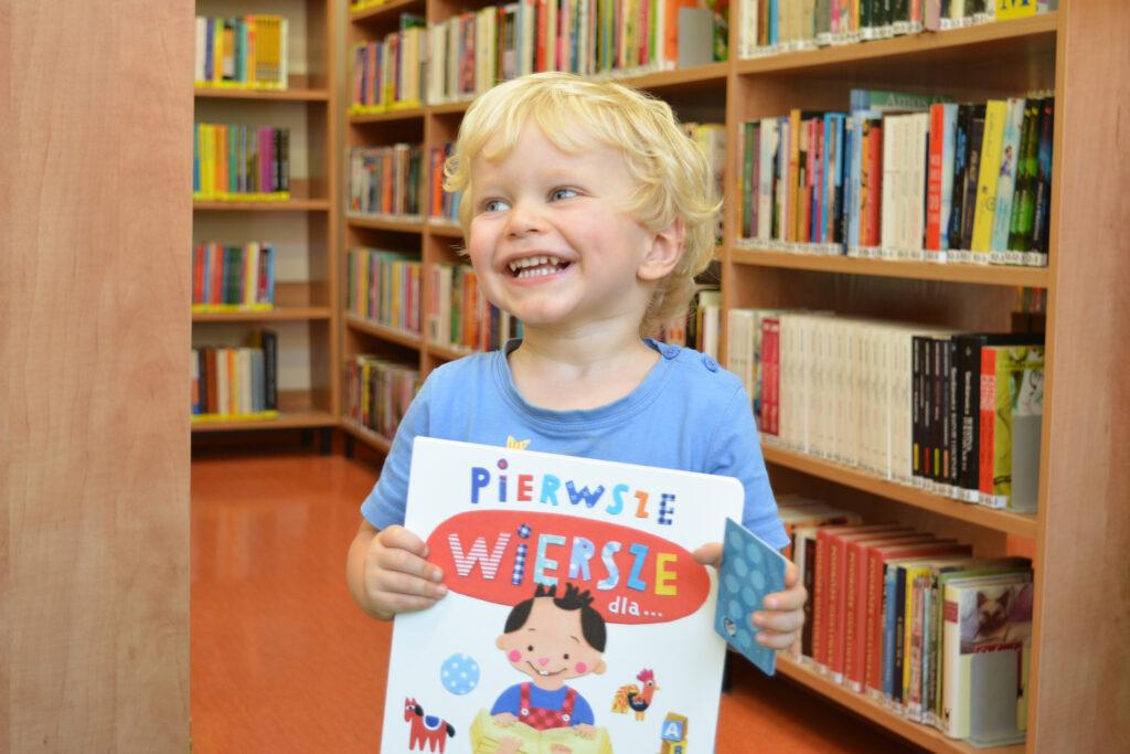 Uśmiechnięte dziecko z książką w ręce. W tle regały z kolorowymi książkami.
