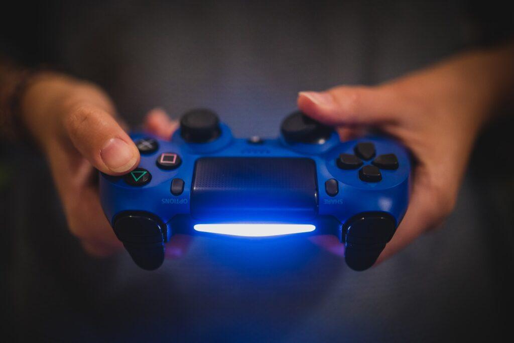 Dłonie trzymają pada do konsoli Sony